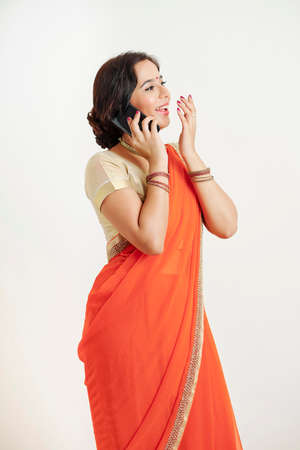 Young Indian woman in traditional dress laughing when talking on phone with friend