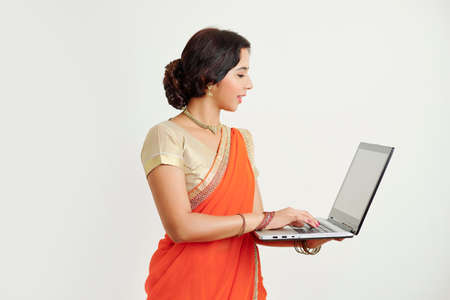 Young Indian woman in traditional orange sari answering e-mails on her laptop, isolated on white