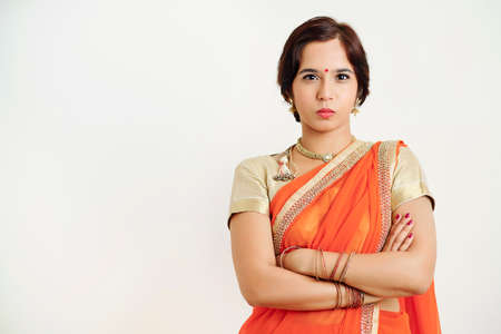 Unhappy young Indian woman in sari dress pouting lips, crossing arms and looking at camera Stock Photo