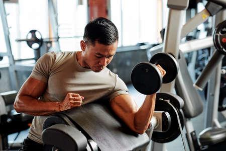 Colocar deportista asiático serio ejercicio con pesas en el gimnasio
