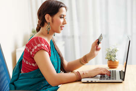 Positive Indian woman in traditional dress paying with credit card for online purchases Banco de Imagens
