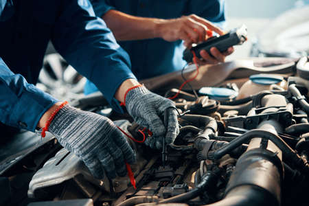 Close-up image of mechanic wearing protective gloves when using multimeter for testing automobile battery 免版税图像