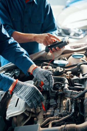 Hands of professional mechanics using professional tool for testing car motor in garage Banco de Imagens
