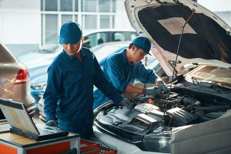 Team of Vietnamese mechanics using computer diagnostics system when checking car motor