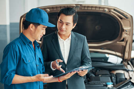 Professional Vietnamese car service worker showing document with list of mechanical failures to client