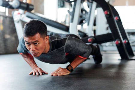 Starker junger asiatischer Mann, der während des Sporttrainings Diamant-Liegestütze im Fitnessstudio macht