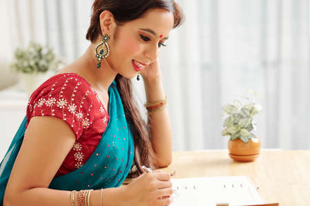 Positive young Indian woman reading plans for the day in opened textbook