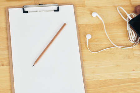 Clipboard with blank paper sheet, pencil and earphones on wooden table