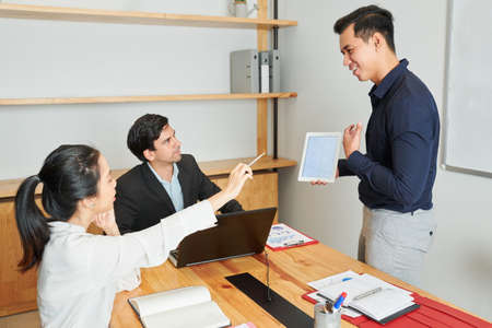 Asian young businessman holding tablet pc and showing online presentation to business people and they discussing it together at business meeting