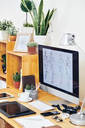 Sketches for new fashion collection on screen of computer on office table of fashion designer or illustrator