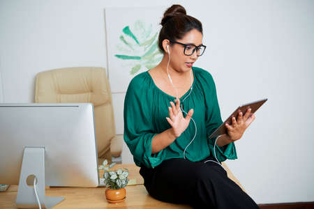 Serious Indian businesswoman in eyeglasses sitting on the table and holding online conference on tablet pc for her colleagues at office