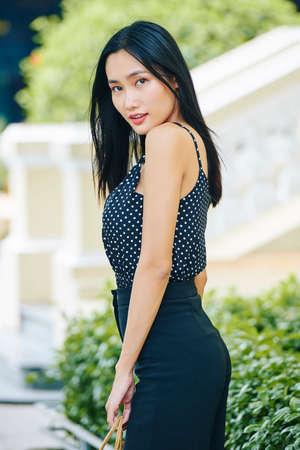 スタイリッシュな服を着て、屋外に立っているカメラを見て、長い黒髪を持つ若いアジアの女性の肖像画