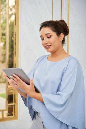 Indian elegant businesswoman standing and using digital tablet for online work at office