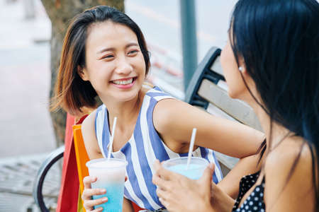 Happy Asian woman drinking fresh cocktail and smiling to her friend while they sitting on the bench in the park Stock Photo