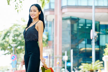 Portrait of Asian young woman in stylish suit holding shopping bags smiling at camera while walking in the city in summer