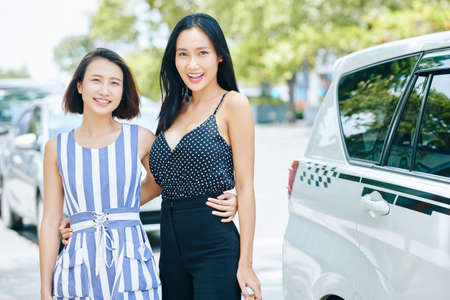 Portrait of two beautiful Asian women embracing each other and smiling at camera while standing near the taxi in the city