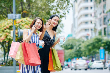 Two Asian young friends with shopping bags and cocktails standing in the city together and waiting for a taxi Banco de Imagens