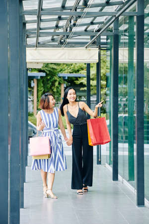 Smiling Asian woman with shopping bags pointing at shop window and showing it to her friend while they going for shopping in the city Banco de Imagens