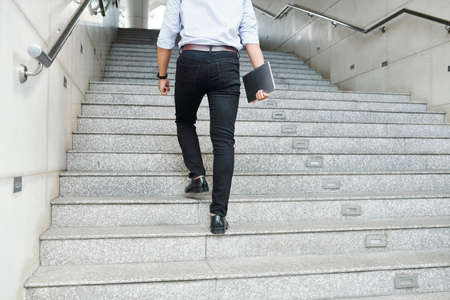 Rear view of young man with digital tablet in hand walking up the stairs and hurrying to office