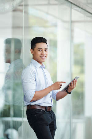 Positive attractive entreprenuer pointing at computer screen in his hands when standing outdoors