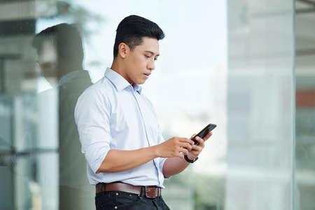 Ernsthafter hübscher junger asiatischer Geschäftsmann, der Textnachrichten in seinem Smartphone überprüft