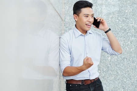Portrait of excited young handsome entrepreneur making fist pump when talking on phone