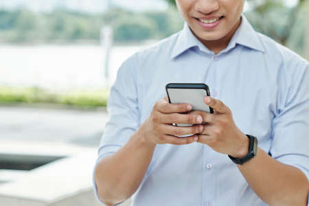 Close-up image of smiling young businessman reading text messages fro his colleagues and clients