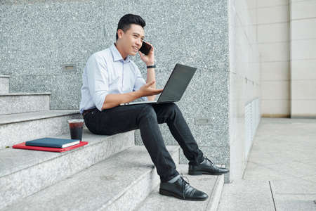 Young positive Asian entrepreneur sitting on steps with laptop and calling on phone to business partner