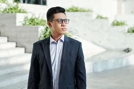 Portrait of young pensive entrepreneur in glasses standing in the street of big city and looking away