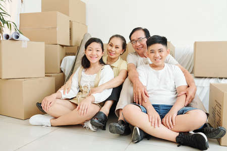 Happy children and grandparents sitting on the floor in living room of new house with many cardboard boxes around