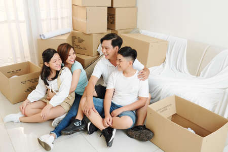 Happy parents hugging their teenage kids when resting on the floor in their new apartment after moving in Reklamní fotografie