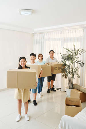 Parent and children holding cardboard boxes with belongings packed for house move