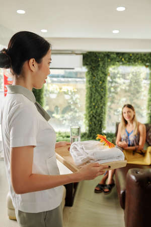 Receptionist of spa salon bringing tray with towels and glass of water to female client Imagens