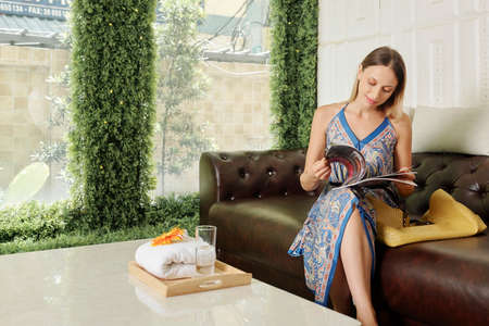 Pretty young Caucasian woman sitting on sofa and reading magazine when sitting in waiting area of spa salon