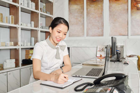 Hübsche lächelnde vietnamesische Spa-Salon-Empfangsdame, die Notizen im Planer macht