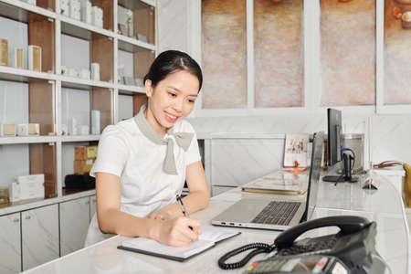 Recepcionista de salón spa vietnamita muy sonriente tomando notas en el planificador