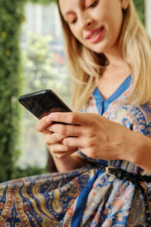Close-up image of young woman checking social media and answering messages Imagens