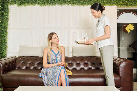 Hospitable smiling Vietnamese spa salon worker bringing tray with glass of fresh water to smiling female client Imagens