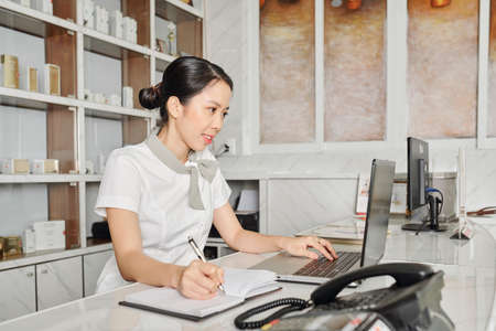 Positive young Asian receptionist reading messages from client on laptop screen and taking notes in planner Imagens