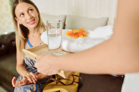 Beautician bringing tray with fresh soft towel, flower and glass of water to female client Imagens