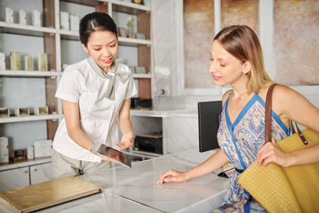 Cheerful Vietnamese spa salon receptionist showing tablet computer with list of procedures and prices