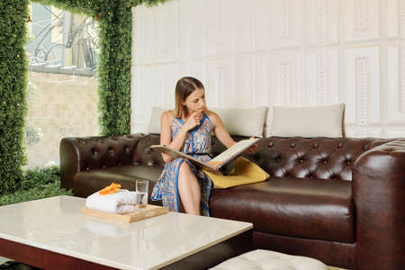 Young woman sitting on sofa in waiting area of spa salon and choosing procedure in big catalog