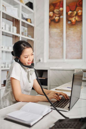 Young Vietnamese female spa salon owner talking on phone with client and working on laptop Imagens