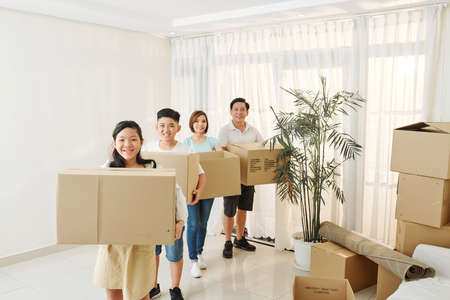 Joyful Vietnamese teenagers and their parents standing in empty living room with cardboard boxes of belongings Imagens