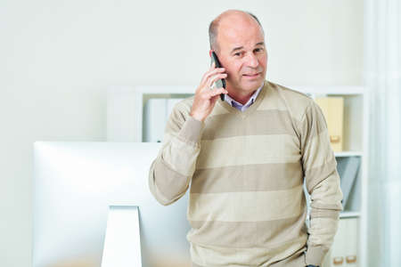 Positive mature business executive in wool sweater making phone call to client or business partner