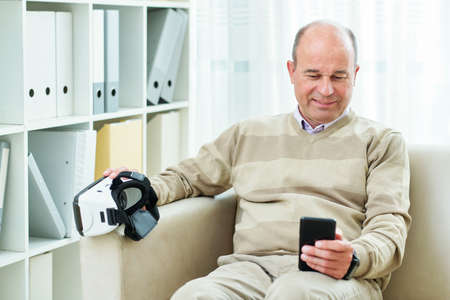 Smiling mature man sitting on sofa and watching tutorial on smartphone before using virtual reality headset for the first time