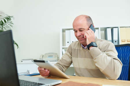 Smiling mature entrepreneur reading information on digital tablet and talking on smartphone with clients when working at his office table Stock Photo