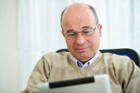 Smiling middle-aged Caucasian man in glasses enjoying reading a book on digital tablet