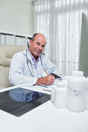 Positive mature cardiologist analyzing cardiogram of patiet and taking notes Imagens