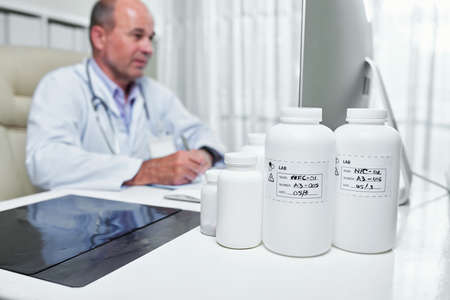 Various bottles with pills and tablets on table of general practitioner